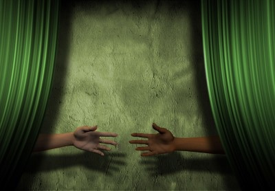 Arms reaching from behind green curtain